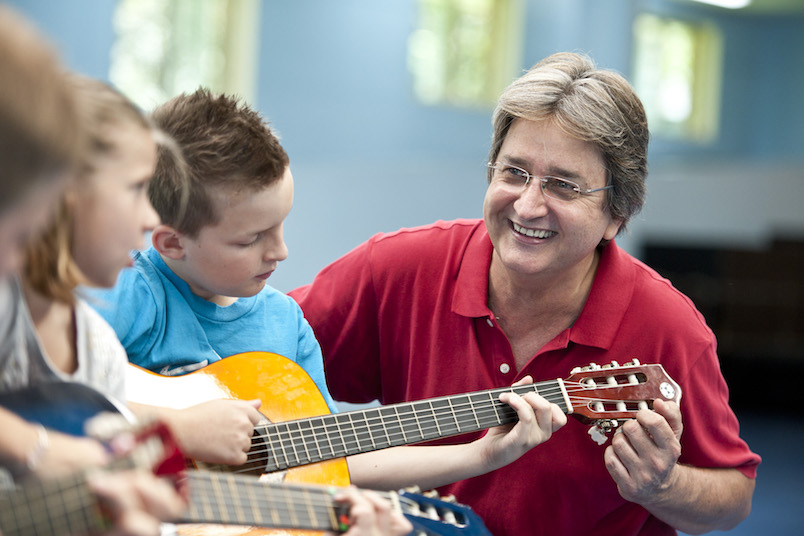 καθηγητης μουσικης διδασκει παιδια κιθαρα